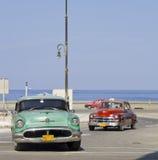 Carros cubanos perto do mar em Havana Foto de Stock Royalty Free