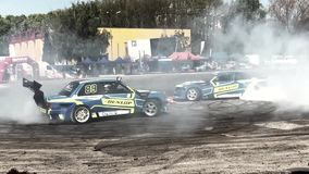 Carros de corridas que derivam e que queimam pneus nos anéis de espuma com Slo-mo filme