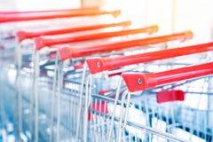 Carros de la compra, carretilla del carro de la compra en los grandes almacenes de la venta al por menor de la fila, concepto de  fotografía de archivo