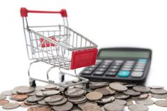 Carros de la compra y calculadora sobre monedas y billetes de banco apilados fotografía de archivo libre de regalías