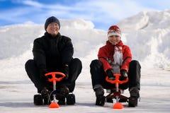 Carros de neve felizes da equitação do homem novo e da mulher Imagem de Stock