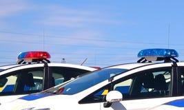 Carros de polícia com as sirenes vermelhas e cor azul Fotografia de Stock