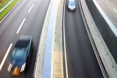 Carros de pressa em pistas da estrada foto de stock royalty free