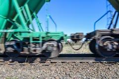 Carros de un tren de carga que se mueve rápidamente a lo largo de los carriles fotografía de archivo