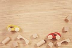 Carros e tijolos de madeira coloridos do brinquedo no fundo de madeira imagens de stock royalty free