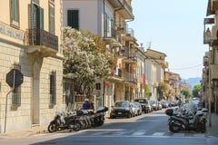 Carros e velomotor estacionados na rua em Viareggio, Itália imagens de stock