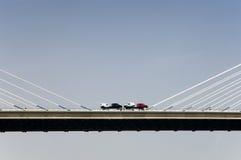 Carros en el puente de suspensión Imagenes de archivo