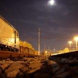 Carros en una pista ferroviaria en la noche Imagenes de archivo