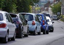 Carros estacionados na rua Fotos de Stock