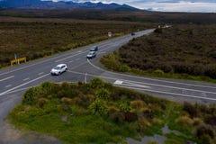 Carros na estrada nova do deserto de Zealands através das montanhas imagens de stock