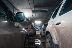Carros no estacionamento iluminado subterrâneo do carro foto de stock royalty free