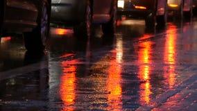 Carros no tráfego, faróis na chuva no asfalto, vista abaixo A chuva bate as poças na noite Reflexão das luzes do carro filme