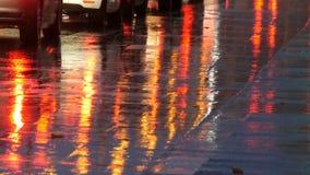 Carros no tráfego, faróis na chuva no asfalto, vista abaixo A chuva bate as poças na noite Reflexão das luzes do carro vídeos de arquivo