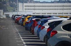 Carros novos alinhados em um parque de estacionamento fotos de stock royalty free