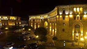 Carros que conduzem lentamente através do quadrado da república da noite em Yerevan, luzes na cidade filme