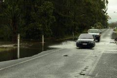 Carros que cruzam a estrada inundada imagens de stock
