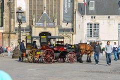Carros que esperan a turistas en cuadrado de la presa en Amsterdam imagenes de archivo