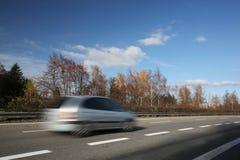 Carros que movem-se rapidamente em uma estrada Fotografia de Stock Royalty Free