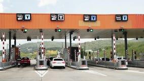Carros que passam através do ponto automático do pagamento em uma estrada com pedágio Ponto da estrada do pedágio, estação do ped video estoque