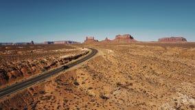 Carros que passam pela câmera do zangão na estrada da estrada do deserto no vale ensolarado dos monumentos nos EUA com skyline li video estoque