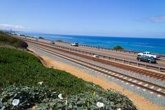 Carros que viajam ao longo da estrada da costa ao lado das trilhas Fotografia de Stock Royalty Free