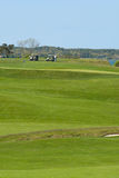 Carros y jugadores de golf en curso en el club de campo Fotos de archivo libres de regalías