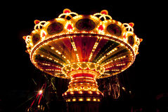 Carrossel chain colorido do balanço no movimento no parque de diversões na noite Foto de Stock