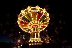 Carrossel chain colorido do balanço no movimento no parque de diversões na noite Fotografia de Stock Royalty Free