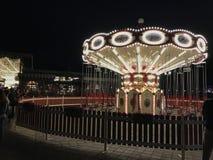 Carrossel circular brilhantemente iluminado na terraplenagem de Kazan em uma noite do verão Os povos montam no carrossel e andam  imagens de stock royalty free