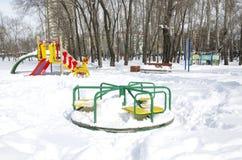 Carrossel em um parque de diversões coberto de neve, público do ` s das crianças Rússia, Sibéria fotografia de stock royalty free