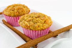 Carrot and Apple Muffins. Home made carrot and apple muffins on a white plate with cinnamon sticks Royalty Free Stock Photo