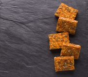 Carrot bars with oatmeal, dried apricots, seeds and honey stock images