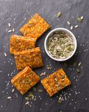 Carrot bars with oatmeal, dried apricots, seeds and honey stock photography