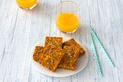 Carrot bars with oatmeal, dried apricots, seeds and honey with orange juice royalty free stock photography