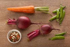 Carrot, beets, pea pods and dried herb on the wood Royalty Free Stock Image