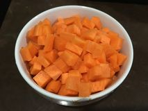 Cut sliced into cube shape carrots and put into white bowl. royalty free stock photography