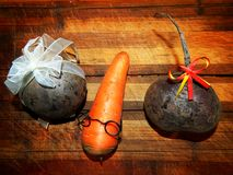 Carrot boy with glasses and two beets with bows Stock Photography