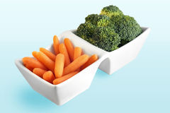Carrot and broccoli. Healthy food choice from the vegetable garden: carrot and broccoli in cute white serving plate Stock Photos