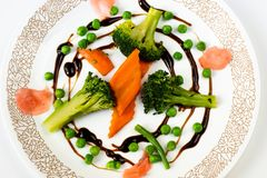 Carrot,broccoli,peas and ginger in balsamico circle on white plate. Healthy and nicely arranged food - stewed carrot, brocoli and peas and pickled ginger in stock images
