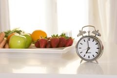 Carrot cake with alarm clock on white table Stock Photo