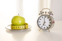 Carrot cake with alarm clock on white table Royalty Free Stock Photography