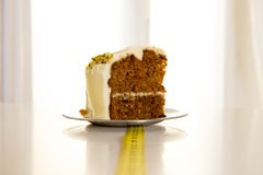 Carrot cake with alarm clock on white table Royalty Free Stock Images