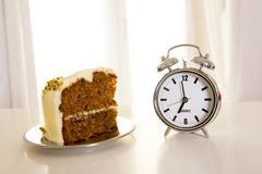 Carrot cake with alarm clock on white table Royalty Free Stock Photos