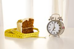 Carrot cake with alarm clock on white table Royalty Free Stock Image