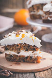 Carrot cake with cinnamon, walnuts and orange cream cheese fro. Sting on rustic wooden table stock photo