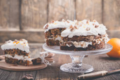 Carrot cake with cinnamon, walnuts and orange cream cheese fro. Sting on rustic wooden table royalty free stock photography