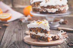 Carrot cake with cinnamon, walnuts and orange cream cheese fro. Sting on rustic wooden table stock photos