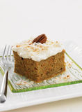 Carrot cake with coconut icing. Piece of carrot cake with grilled coconut icing and pecan. With fork and glass plate royalty free stock images