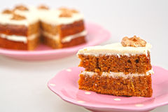 Carrot cake with cream cheese. Frosting in a pink on white background stock photos