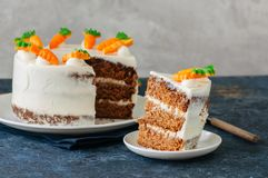 Carrot cake with cream cheese frosting decorated with carrot mar. Malade serving on a plate on a blue stone background royalty free stock photography